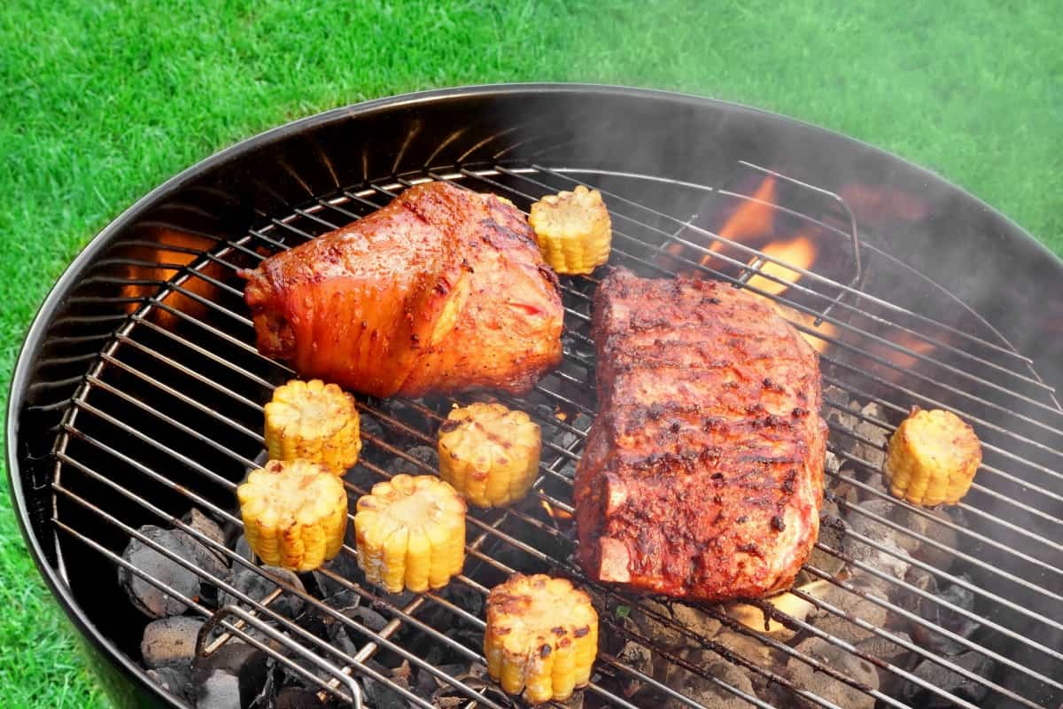 A charcoal grill with corn and ribs on