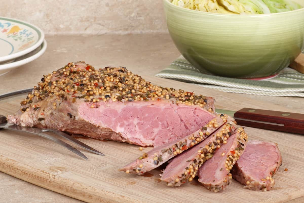 Sliced corned beef on a cutting board with a bowl of cabbage