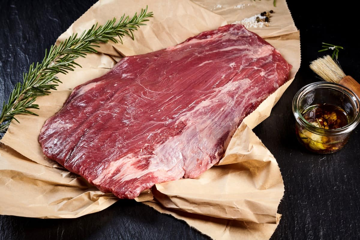Raw flank on butcher paper, with a rosemary sprig