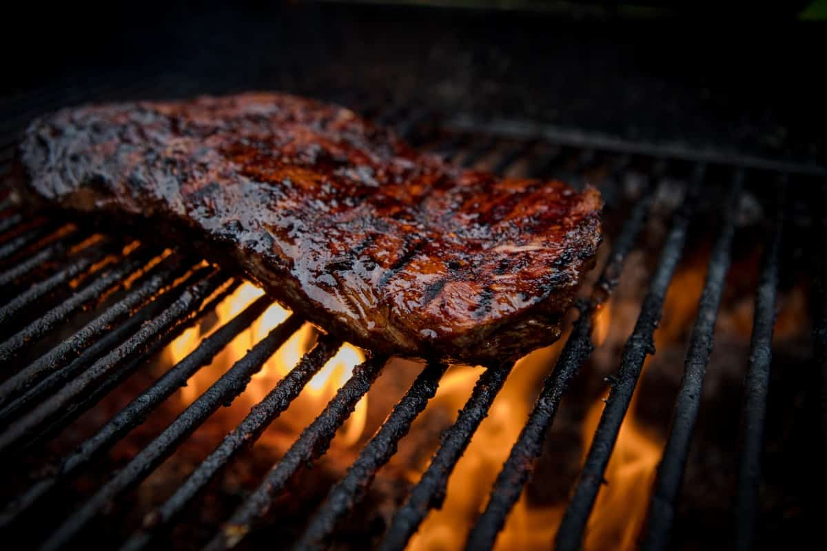 Flank steak being seared on on a flaming grill