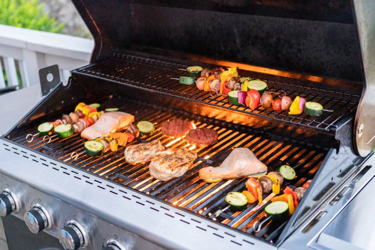 A gas grill loaded with Atlantic salmon and vegetable kebabs