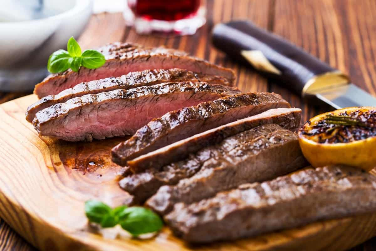 grilled and sliced flank steak on a wooden cutting board with a grilled an charred lemon half