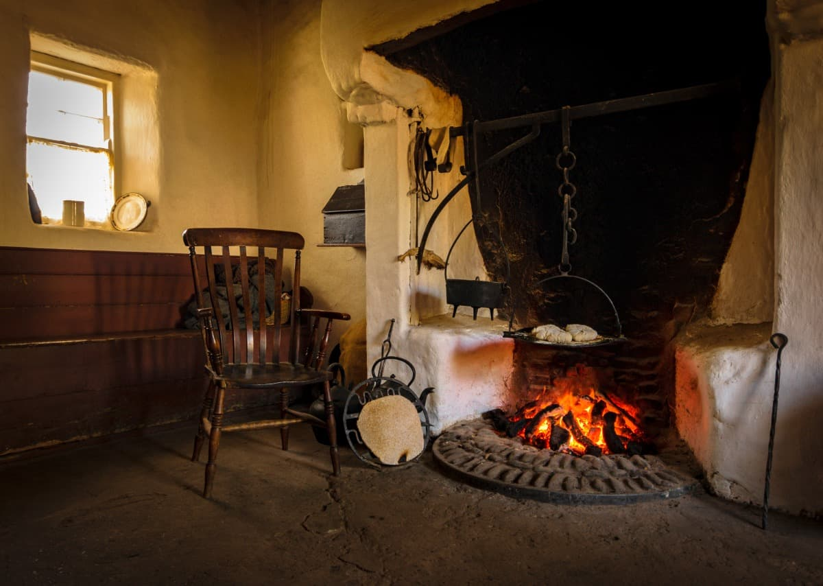 A wooden chair in a vintage style kitchen, with tools and fireplace for cooking