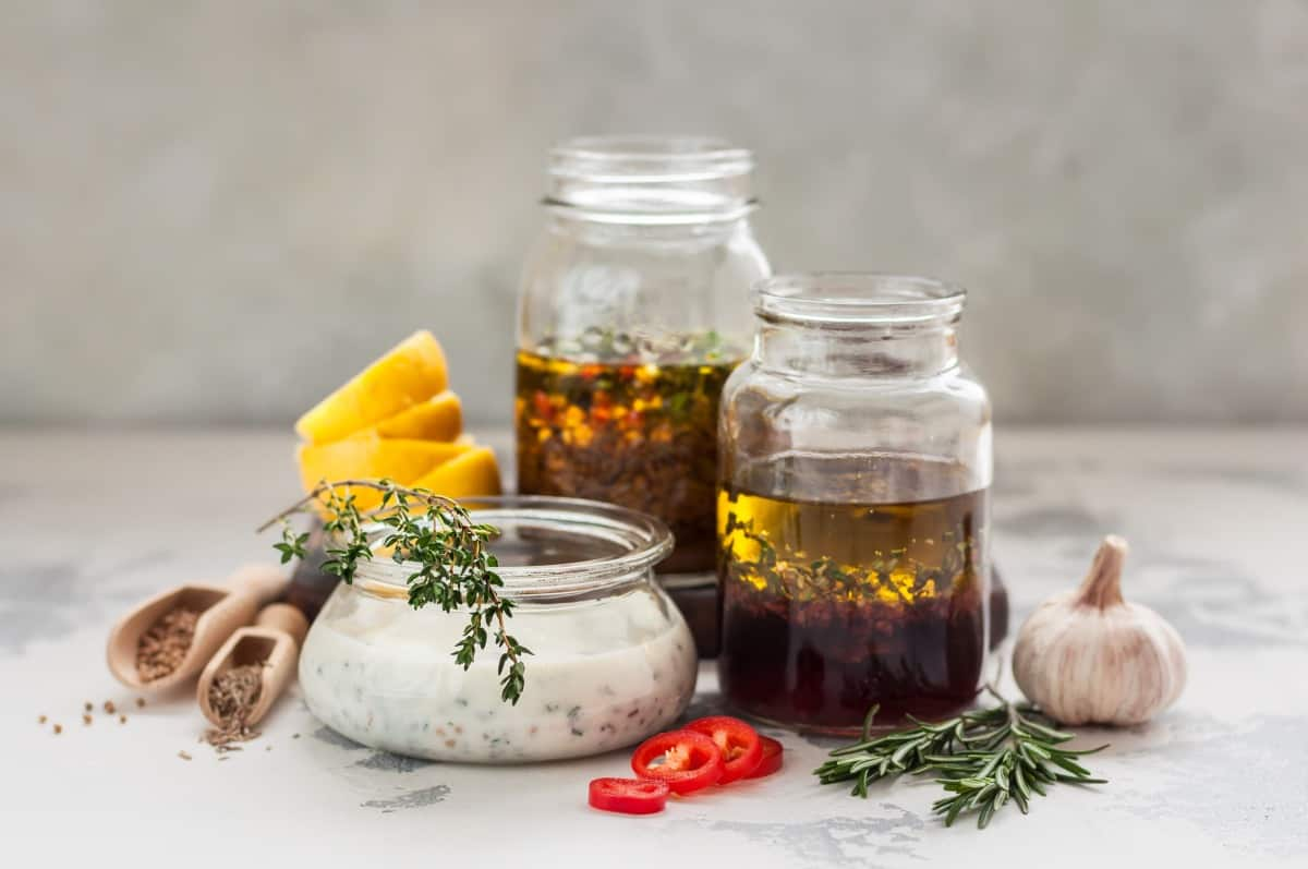 An assortment of 3 meat marinades in clear jars on a table