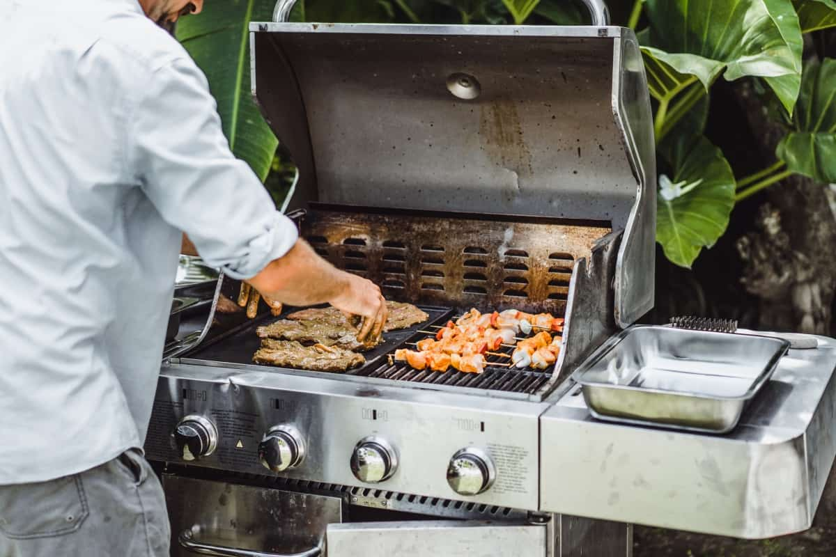 A man grilling meat on a gas grill