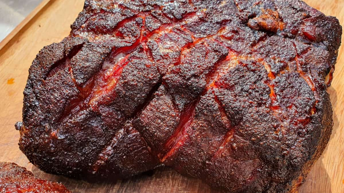 A smoked pork butt with crisscross scoring on a cutting board