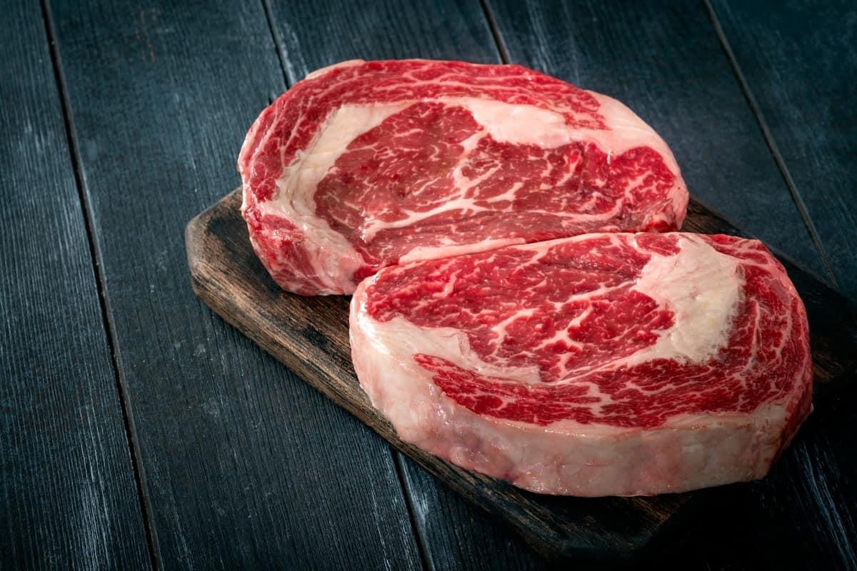 Two prime ribeye steaks on a dark surface
