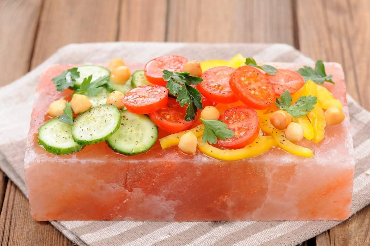 A vegetable salad chilling on a pink salt block