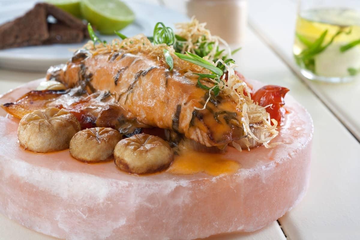 salmon and potatoes cooking on a round Himalayan salt block