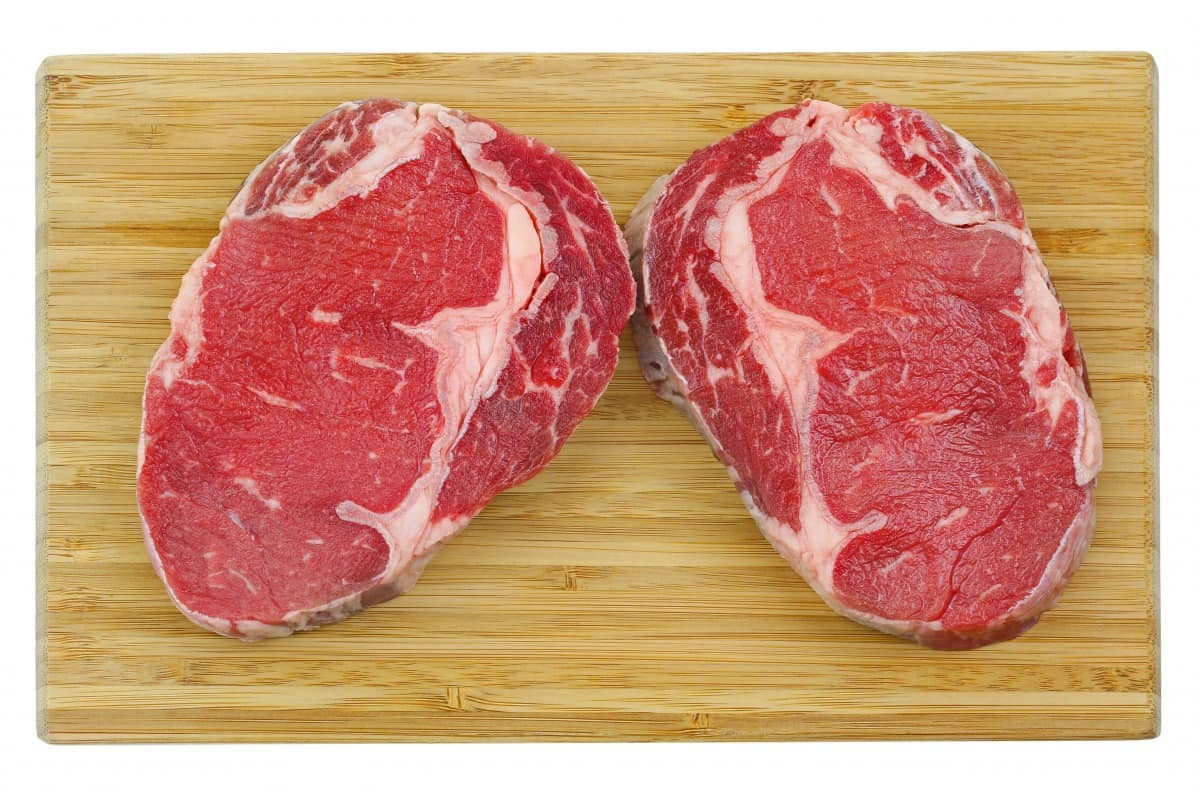 Two select ribeye steaks on a wooden cutting board