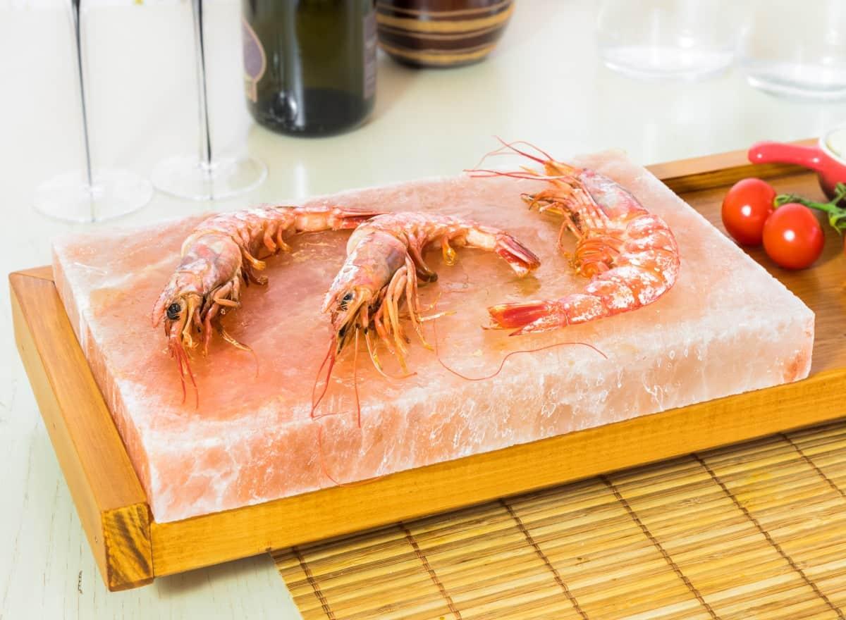 3 giant shrimp being cooked on salt block