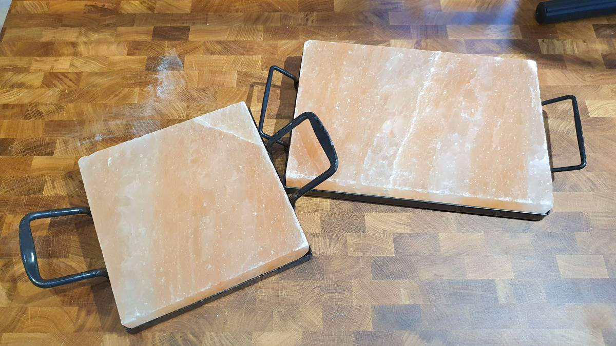 Two different sized salt blocks on a wooden table
