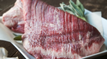 Close up of some flank steak in ceramic cookware with some rosemary