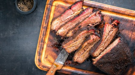 A smoked and sliced wagyu brisket on a cutting board