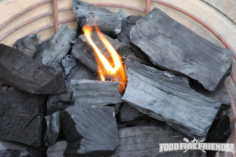 Lumpwood charcoal being lit inside of a kamado grill
