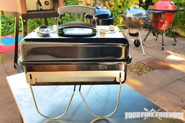 A Weber go anywhere tabletop grill on a work surface with many BBQs in the background