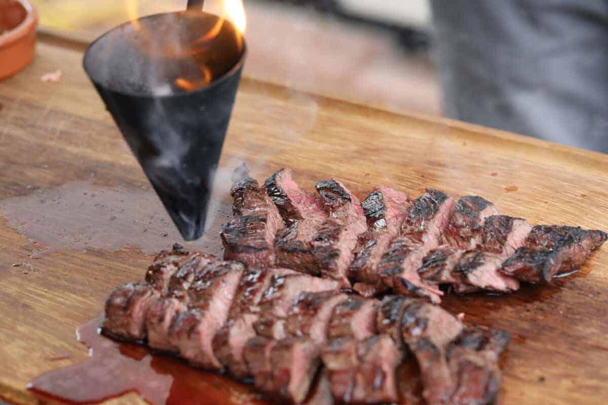 The flambadou dripping flaming bone marrow onto sliced hanger steak