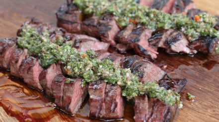 Grilled, sliced hanger steak with chimichurri on a large wooden chopping board