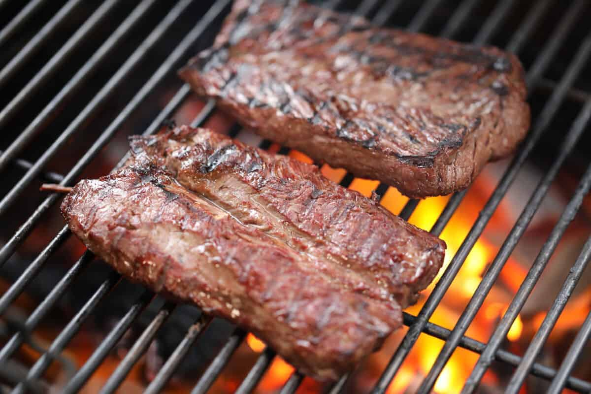2 hanger steaks being seared on a screaming hot grill
