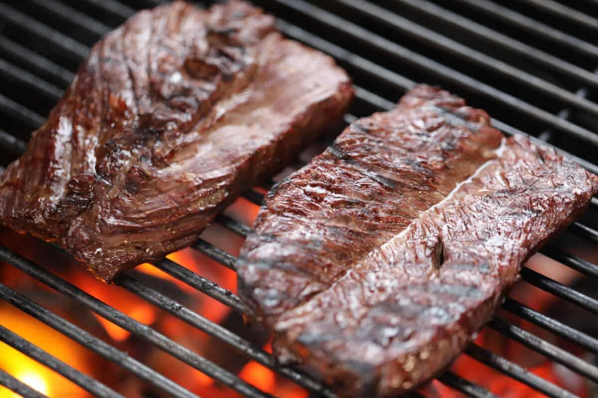 Hanger steak on a grill with red hot coals seen below