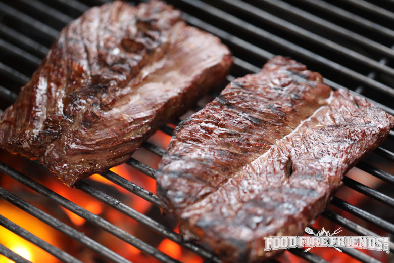 Hanger steak on a grill with red hot coals seen below