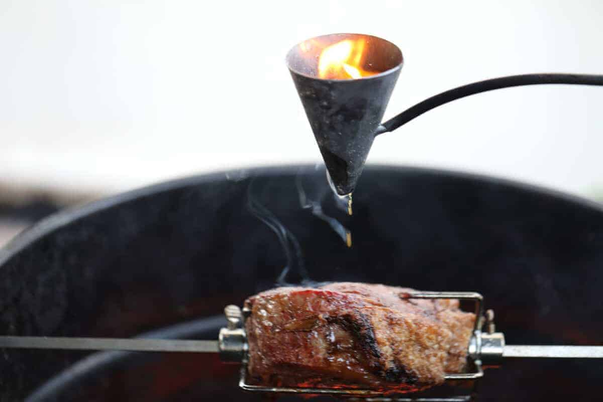 A flambadou dripping flaming fat onto a sirloin roast on a rotisserie