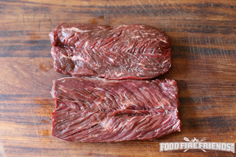 overhead view of 2 raw hanger steaks on a large wooden chopping board