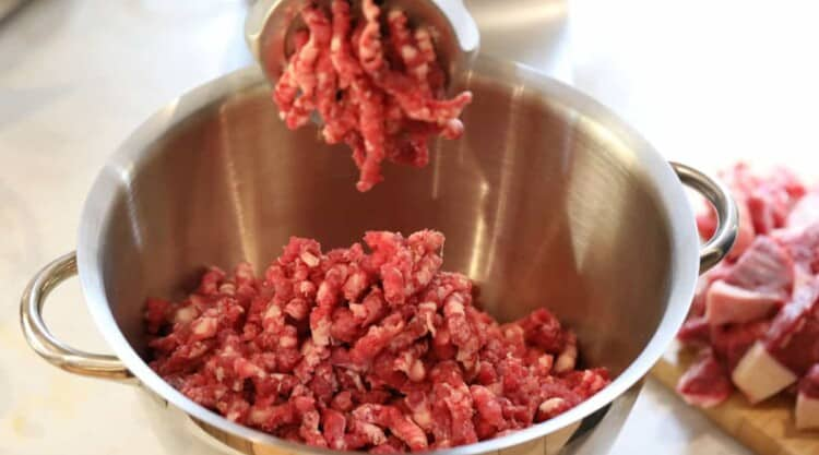 Close up of an electric meat grinder being used to grind beef for burgers