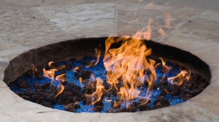 A gas fire pit sunken into a stone table, with orange flames licking out above the rim