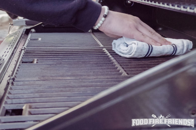 Man wiping down some grill grates with a tea towel
