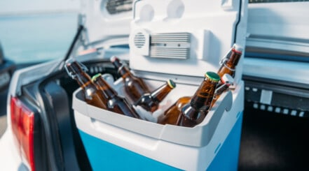 A cooler full of beers in the trunk of a car