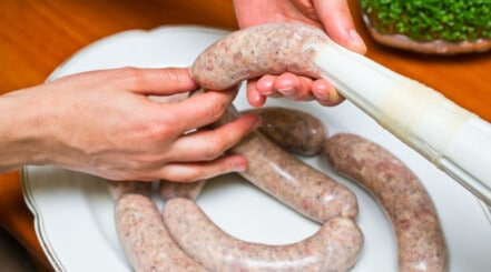 Close up of sausages being stuffed into natural skins from a tube