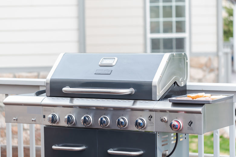 Frame filling shot of a large, high end gas grill in black and stainless steel