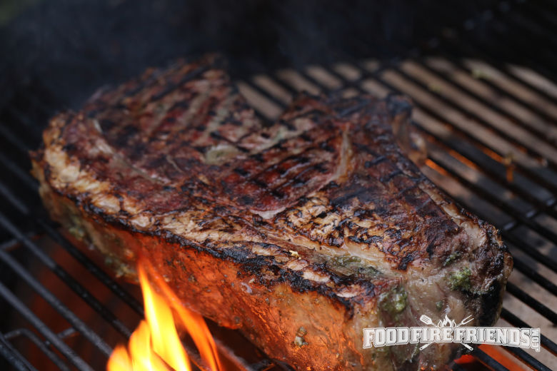 A well seared steak being licked by flames on a grill.