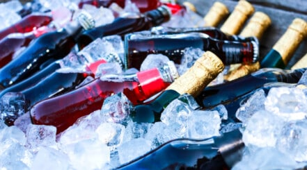 an assortment of bottles on ice in a wheeled cooler