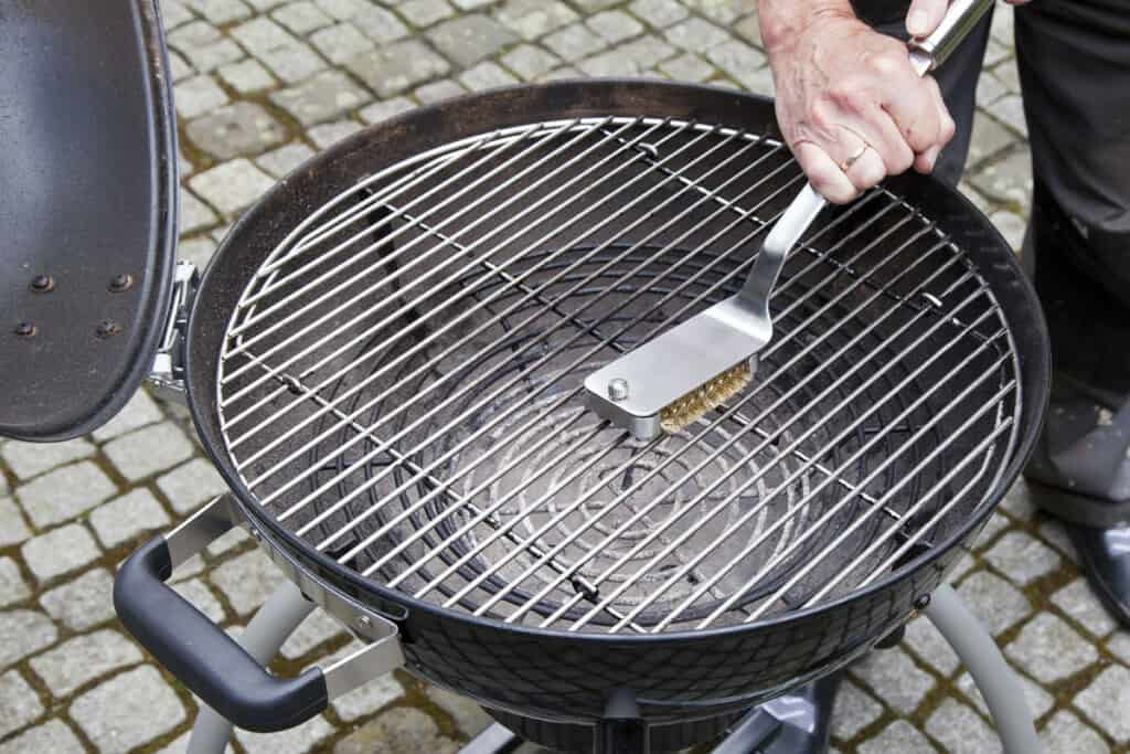 Cleaning a grills grates with a grill brush
