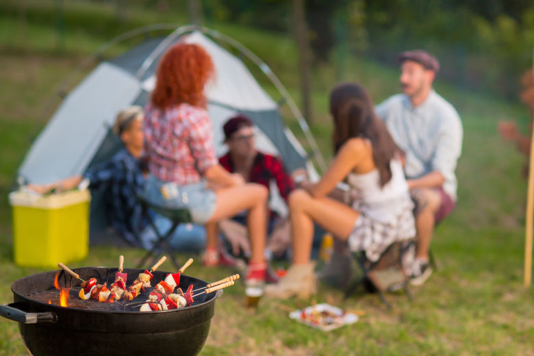 Close up of a camping grill, with a blurred background of a family camping