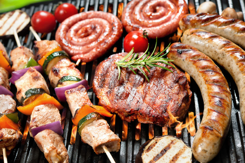 A fully loaded grill, covered in meat cooking over flames