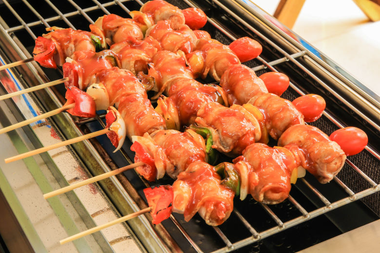 Bacon wrapped sausages on sticks, cooking on an infrared grill