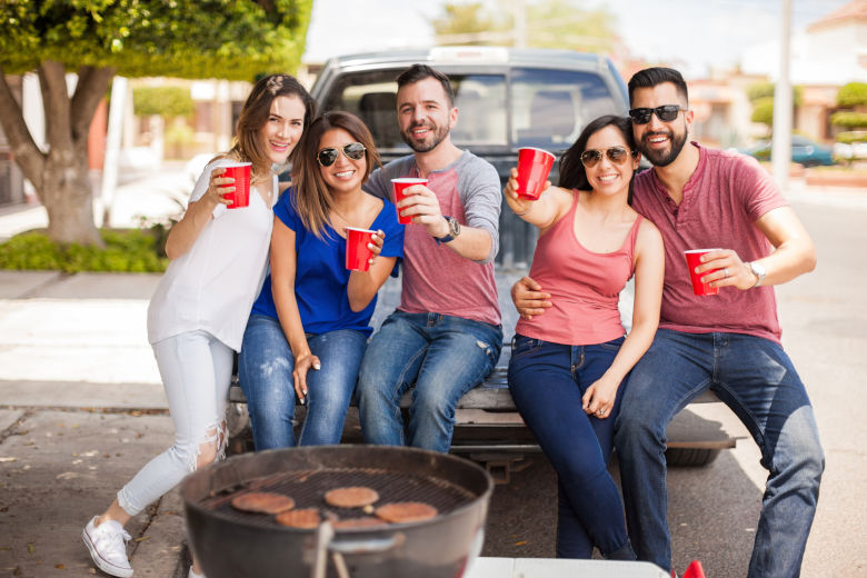 A group of friends tailgating, grilling and drinking from red cups