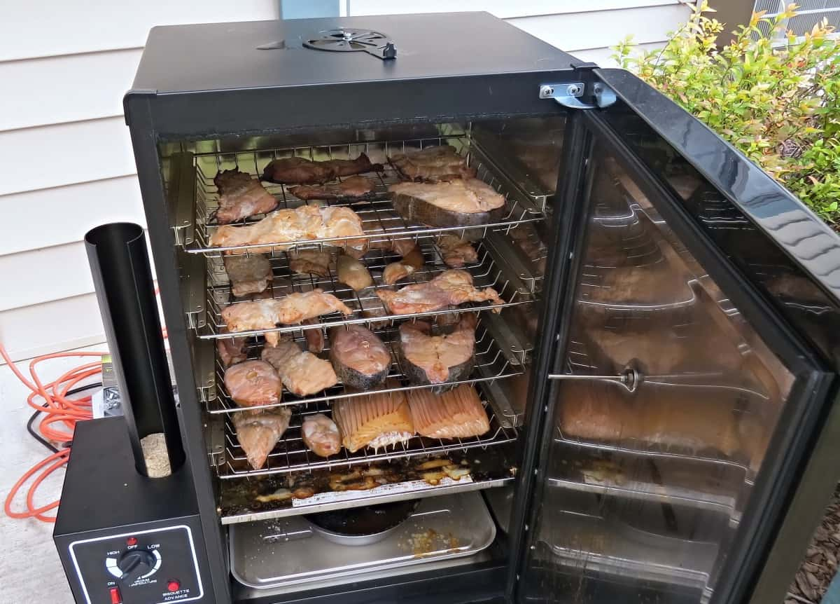 An electric smoker, door open, and it fully loaded with meat and fish