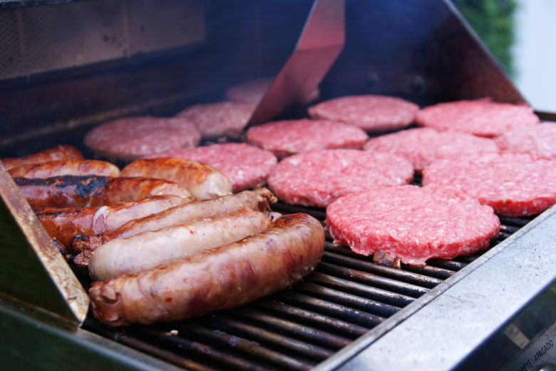 Burgers and sausages being grilled on a gas grill outdoors