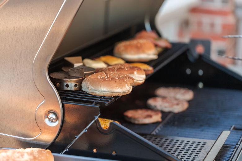 Beefburgers cooking on a gas grill outdoors