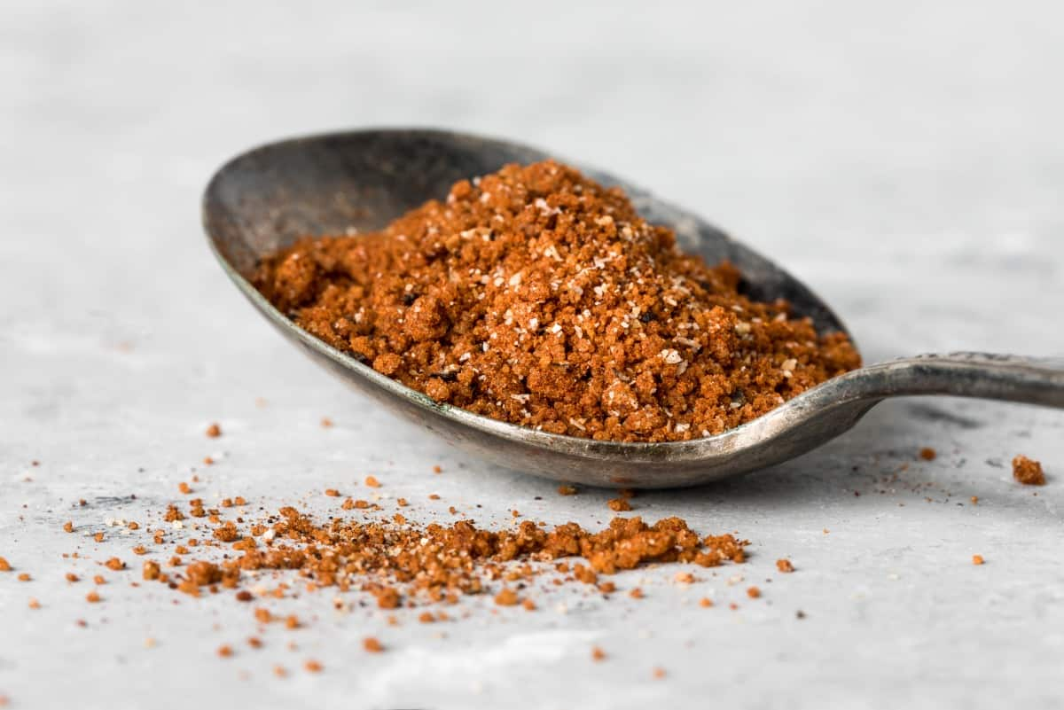 A tablespoon of dry rub, on a white cloth, with a little spilling from the spoon