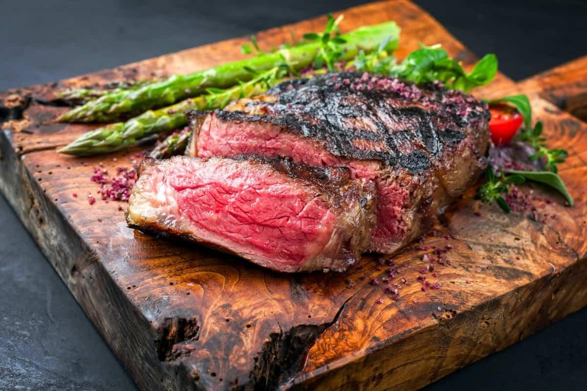 A grilled, sliced, medium rare steak on a cutting board with asparagus.