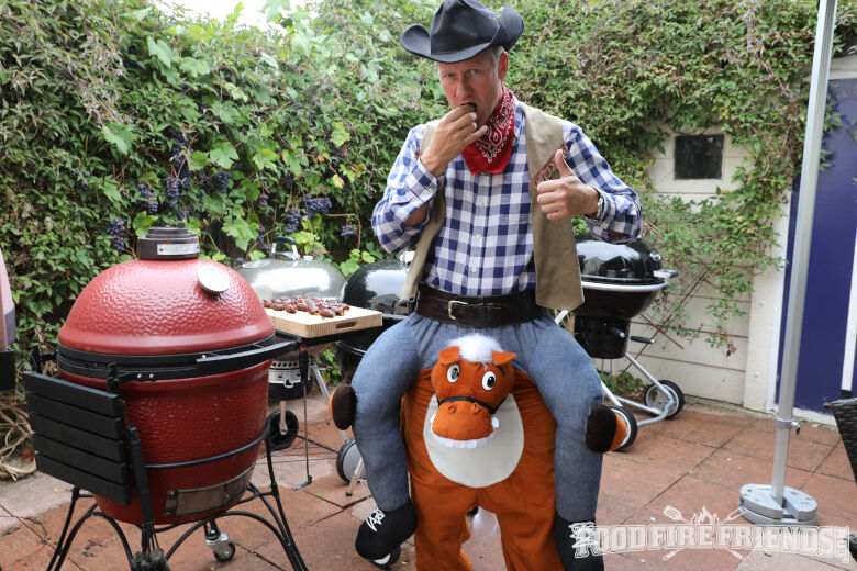 A man in fancy dress eating ABTs next to a red kamado joe grill