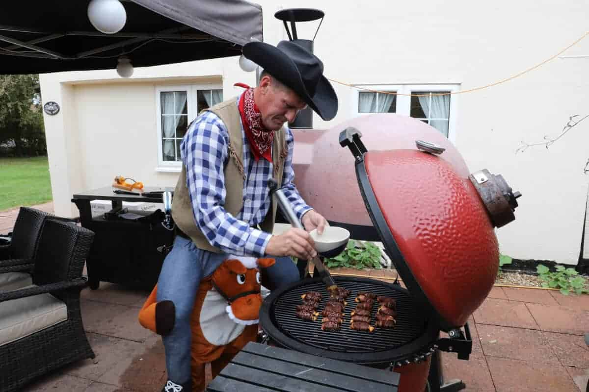 A man in fancy dress adding bbq sauce to ABTs on a kamado grill