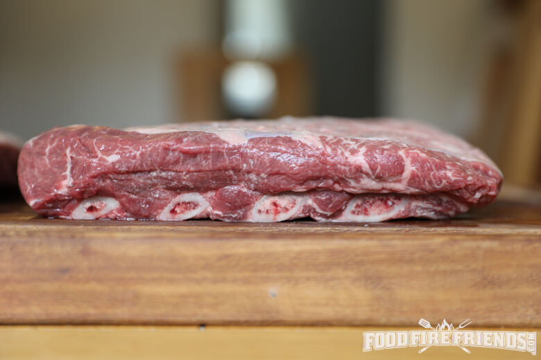 side view of a rack of beef short ribs showing the marbling