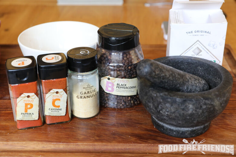 A pestle and mortar, and dry rub ingredients including pepper, salt, paprika, and a couple others