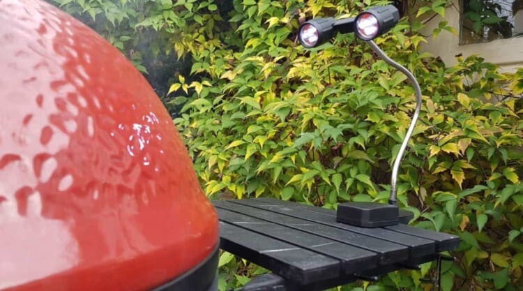 Flexible grill light attached to a red Kamado Joe side table
